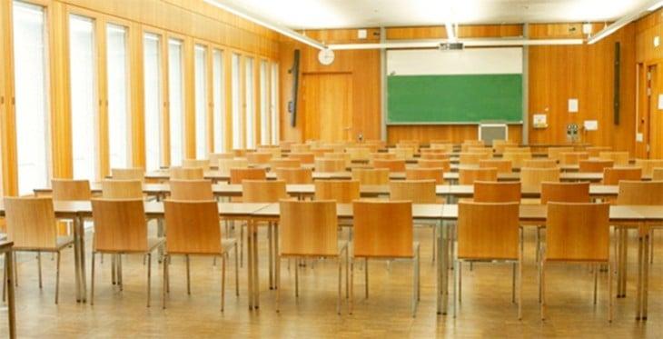 Seminarraum mit Reihen von Holzstühlen und grüner Tafel